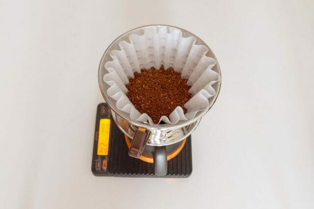 Kalita Wave filled with coffee on top of a mug and scale