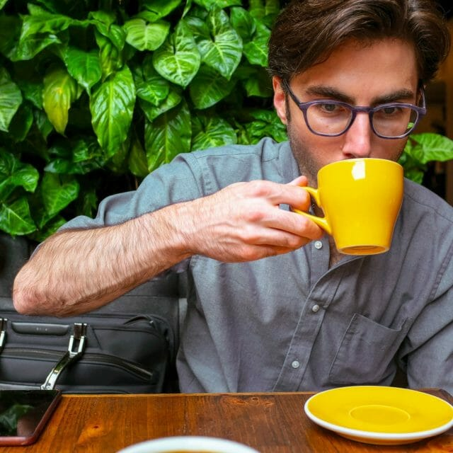 Smiling Coffee Snob drinking from a yellow mug with leaves in the background.