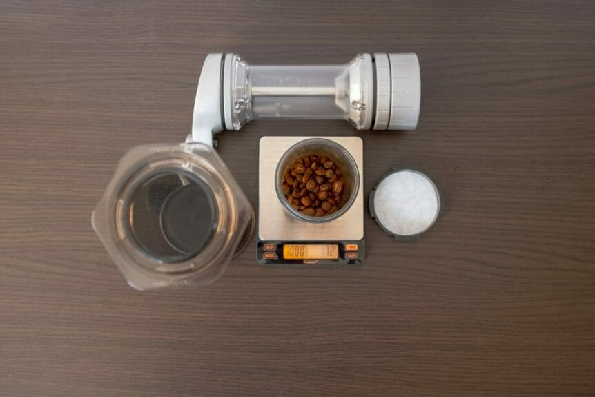 Empty Aeropress set up for inverted method with coffee beans on a scale and a manual coffee grinder on the table.