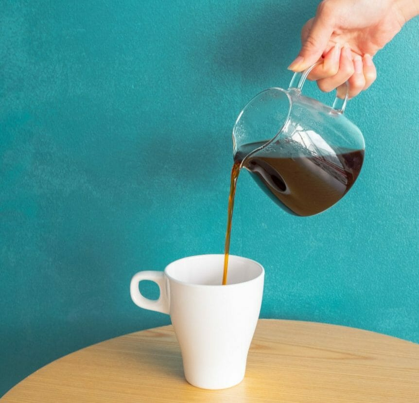 Hand pouring coffee from a glass carafe to a mug with a blue background.