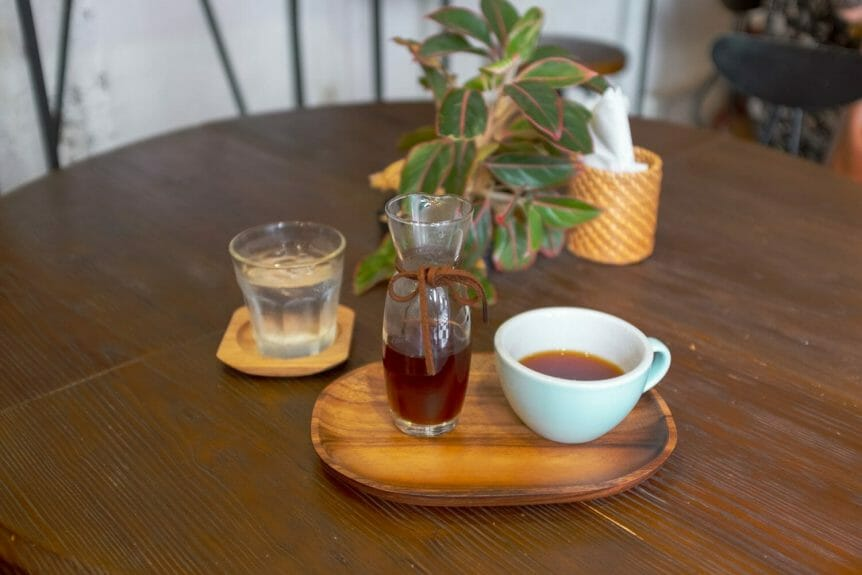 Coffee display on a wooden table. Glass carafe and ceramic cup on a wooden tray with a glass of water and a plant in the background