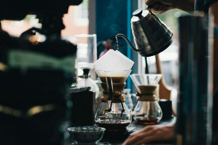 Coffee kettle slowly dripping over a chemex with blurred coffee equipment in the background