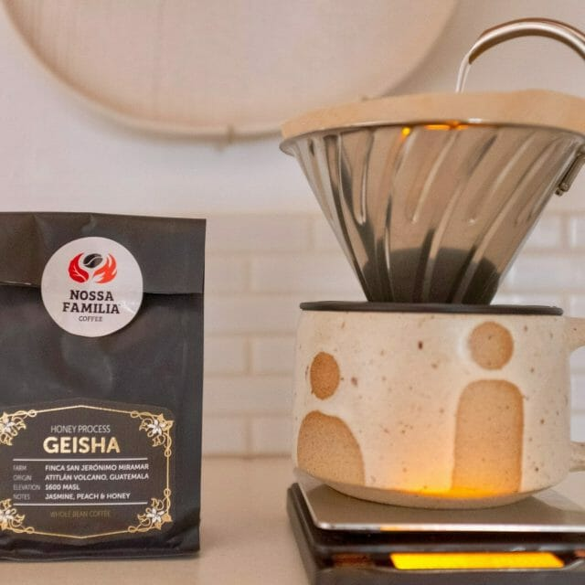 Bag of geisha coffee beans using the honey process with a coffee dripper next to it
